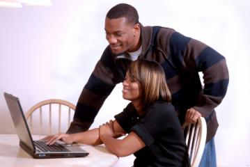 Man and woman looking at a computer